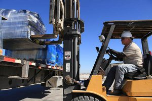 Forklift loading pallet onto semi-truck